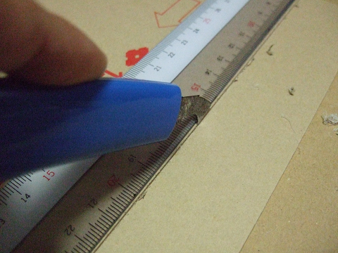 定規にカッターをあて、少しづつアクリルを削っていきます。