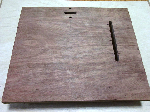 市販の「ディスクグラインダースタンド」の「ベース(土台の板)」に空いている穴と同じ場所に穴を開けた「ベニヤ板」